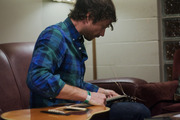 Alex Brown Church strings his guitar in Lincoln Hall's green room.